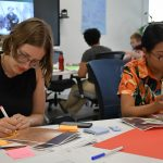 Research associate Nicole Ritchie (left) and research assistant Mika Castro working on their imagined exhibits.